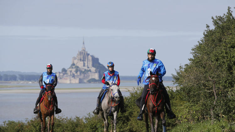 United Arab Emirates' Sheik Hamdan bin Modh Al Maktoun on his horse Yamamah leads the race during Endurance Race of the FEI World Equestrian Games, near Sartilly, western France, Thursday, Aug. 28, 2014. Le Mont Saint Michel is seen in background. (AP Photo/David Vincent)