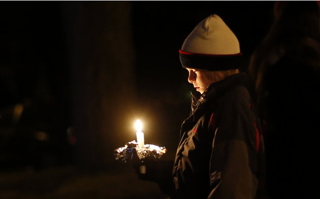 A mourner attends a candlelight vigil at Ram's Pasture to remember shooting victims, Saturday, Dec. 15, 2012, in Newtown, Conn.  A gunman walked into Sandy Hook Elementary School in Newtown on Friday