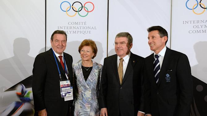 International Olympic Committee President Thomas Bach, second from right, and his wife Claudia, second from left, pose with former German Chancellor Gerhard Schroeder, left, and former British athlete and chairman of the London 2012 Olympic committee Sebastian Coe before the IOC President's Gala Dinner on the eve of the opening ceremony of the 2014 Winter Olympics, Thursday, Feb. 6, 2014, in Sochi, Russia. (AP Photo/Andrej Isakovic, Pool)