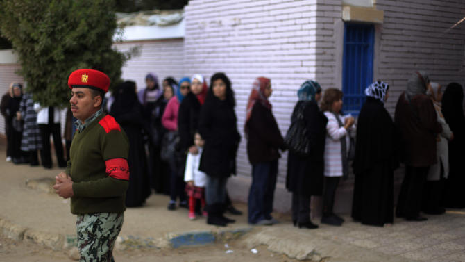 An Egyptian soldier stands guard outside a polling site during a referendum on a disputed constitution drafted by Islamist supporters of President Mohammed Morsi in Cairo, Egypt, Saturday, Dec. 15, 2012. Egyptians were voting on Saturday on a proposed constitution that has polarized their nation, with Morsi and his Islamist supporters backing the charter, while liberals, moderate Muslims and Christians oppose it. (AP Photo/Khalil Hamra)