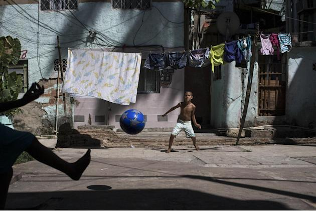 In this Sunday, March 16, 2014 photo, Igor Meireles, 8, center, plays goalkeeper as he prepares to block a kick from his brother Iago Meireles, 10, during their soccer game in the small square next to