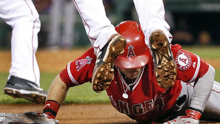Los Angeles Angels' Collin Cowgill dives back safely to third base after running past it on a soft ground-ball single by Albert Pujols in the ninth inning of a baseball game against the Boston Red Sox at Fenway Park in Boston, Wednesday, Aug. 20, 2014. The Angels won 8-3. (AP Photo/Elise Amendola)