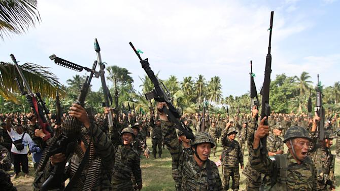 """Members of the Moro Islamic Liberation Front shout """"Allahu Akhbar,"""" or God is great, as they gather at their stronghold at Camp Darapanan in Maguindanao province in southern Philippines to coincide with the tentative peace-signing agreement between MILF and the Government at Malacanang Palace in Manila, Philippines, Monday, Oct. 15, 2012. (AP Photo/Karlos Manlupig)"""