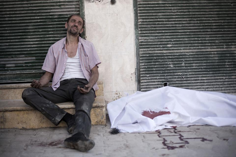 A man cries near the body of his brother, killed by a Syrian Army sniper, near Dar El Shifa Hospital in Aleppo, Syria, Thursday, Sept. 27, 2012. (AP Photo/Manu Brabo)