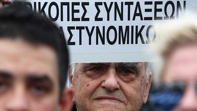 Greek army retirees holding banners with anti austerity slogans, take part in a protest against pension and health cuts in Thessaloniki, Greece on Wednesday, March 13, 2013. Hundreds of retired armed forces officers, many with their families, protested over cuts in their pensions. Greece has resorted to severe cuts in pensions and wages in order to pare down its debt. (AP Photo/Nikolas Giakoumidis)