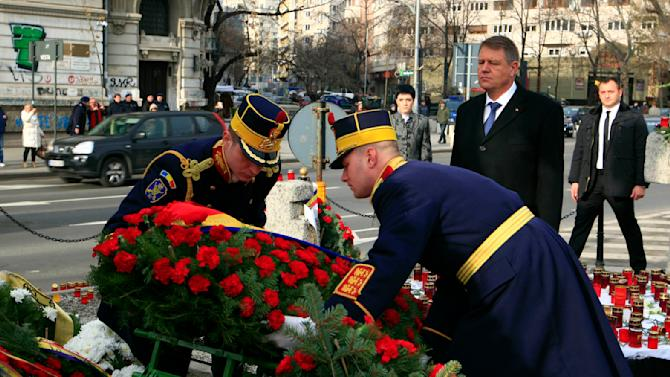 Romanian President Iohannis lays a wreath in front of a monument at the University Square during a ceremony to commemorate the victims of the 1989 revolution in Bucharest