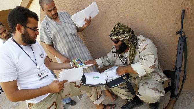Libya rebel local military chief and mosque preacher Sheikh Hussein Furjani, right,  checks a bag of documents found in a house of suspected Gadhafi supporter during a raid in Khalet El Furjan district inTripoli, Libya, Tuesday, Sept. 6, 2011. Rebel fighters, weapons drawn, burst into houses of suspected Gadhafi supporters, searching rooms and hauling away military uniforms, a looted safe and documents linking homeowners to the former regime. (AP Photo/Francois Mori)