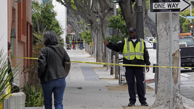 A Santa Monica Police Community Service Officer directs a pedestrian away from the barricaded area where a mountain lion was found in the courtyard of an office building on Second Street in the downtown urban core of Santa Monica, Calif., Tuesday, May 22, 2012.  Discovered shortly before 6 a.m. by a maintenance worker, animal officers and police tried several less-than-lethal methods to subdue the cat, but it continued to try to move out of the area and was shot and killed by police. Many area workers and shoppers were kept out of the area for hours.(AP Photo/Reed Saxon)
