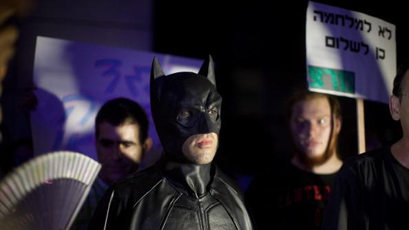 A man dresses in a Batman costume as Israelis demonstrate against a possible Israeli military attack and the threat of war with Iran on August 12, 2012 in Tel Aviv, Israel. Israeli Prime Minister Benjamin Netanyahu has re-affirmed that he sees the greatest threat to Israel's security coming from what is perceived to be a renewed effort by Israel to obtain nuclear weaponry. Concerns have been raised by many observers that Israel may seek to take military action in the face of such a threat, despite requests from the United States and other nations that international diplomacy should be followed in addressing the issue. (Photo by Uriel Sinai/Getty Images)