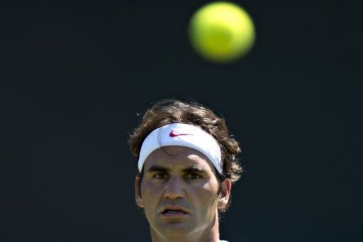 Roger Federer of Switzerland watches the ball as he takes part in a training session