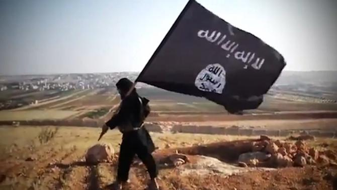 A member of Ussud Al-Anbar (Anbar Lions), a jihadist group affiliated to the Islamic State militant group, holding up the trademark black and white Islamist flag