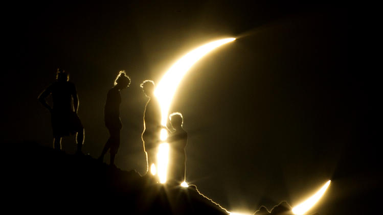 Hikers watch an annular eclipse from Papago Park in Phoenix on Sunday, May 20, 2012. The annular eclipse, in which the moon passes in front of the sun leaving only a golden ring around its edges, was visible to wide areas across China, Japan and elsewhere in the region before moving across the Pacific to be seen in parts of the western United States. (AP Photo/The Arizona Republic, Michael Chow)
