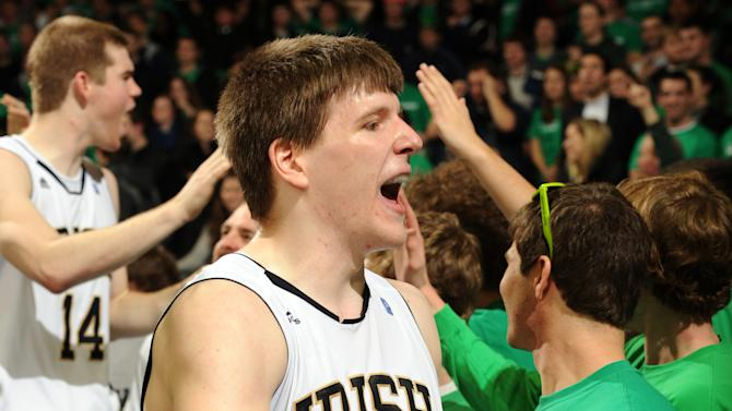 Notre Dame forward Jack Cooley celebrates with students following their 71-44 victory over West Virginia in an NCAA college basketball game Wednesday, Feb. 22, 2012, in South Bend, Ind. Cooley scored 13 points. (AP Photo/Joe Raymond)