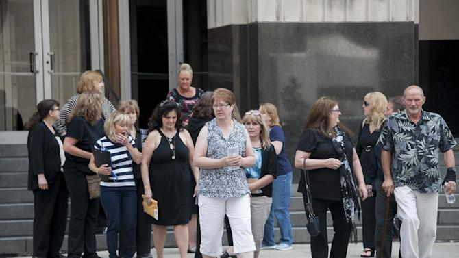 Victims and their families walk across the street from the federal courthouse after testimony was heard in the sentencing hearing of cancer doctor Farid Fata, Monday, July 6, 2015 in Detroit. Fata is headed to prison for fraud and other crimes. But U.S. District Judge Paul Borman first is hearing from experts and former patients about the extent of his scheme to reap millions of dollars from Medicare and other health programs. (David Guralnick/Detroit News via AP)  DETROIT FREE PRESS OUT; HUFFINGTON POST OUT; MANDATORY CREDIT
