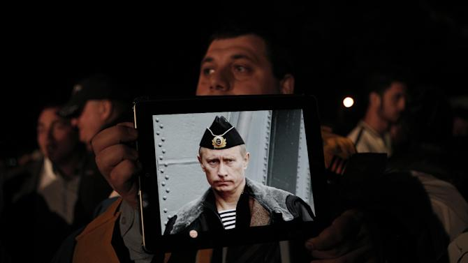 """A Russian man resident in Cyprus holds a tablet with a  picture of Russian President Vladimir Putin during a protest outside the Cypriot parliament, on  Friday, March 22, 2013. Cypriot authorities were putting the final touches Friday to a plan they hope will convince international lenders to provide the money the country urgently needs to avoid bankruptcy within days. """"The next few hours will determine the future of this country,"""" said government spokesman Christos Stylianides.(AP Photo/Petros Giannakouris)"""