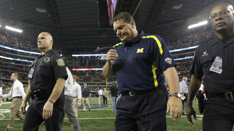 Michigan head coach Brady Hoke, center, walks off the field after an NCAA college football game against the Alabama at Cowboys Stadium in Arlington, Texas, Saturday, Sept. 1, 2012. Alabama  won 41-14.  (AP Photo/LM Otero)