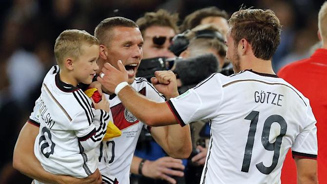 Germany's Lukas Podolski holds is son as he celebrates with Mario Goetze, right, after the World Cup final soccer match between Germany and Argentina at the Maracana Stadium in Rio de Janeiro, Brazil, Sunday, July 13, 2014. Germany beat Argentina 1-0 to win the World Cup