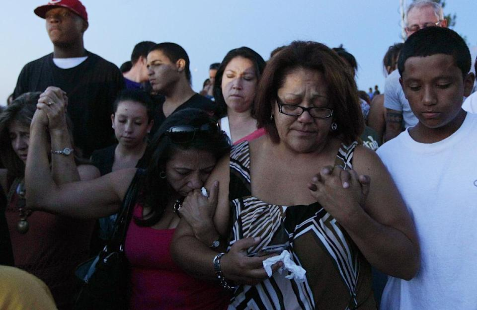 People hold hands as they pray during a vigil, Friday, July 20, 2012, in Aurora, Colo., across the street from the movie theater where a gunman killed at least 12 people and wounded dozens of others Friday in one of the deadliest mass shootings in recent U.S. history. (AP Photo/Ted S. Warren)