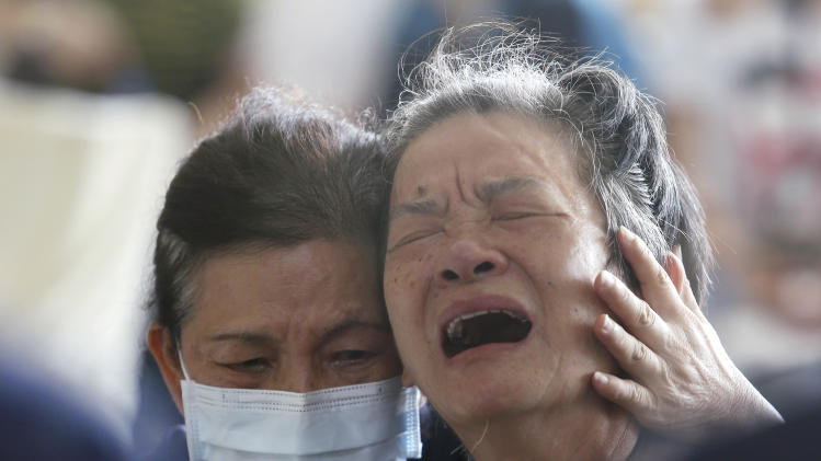 A relative, right, of a victim in the multiple explosions from an underground gas leak is consoled during a funeral service in Kaohsiung, Taiwan, Friday, Aug. 1, 2014. A series of explosions about midnight Thursday and early Friday ripped through Taiwan's second-largest city, killing scores of people, Taiwan's National Fire Agency said Friday. (AP Photo) TAIWAN OUT