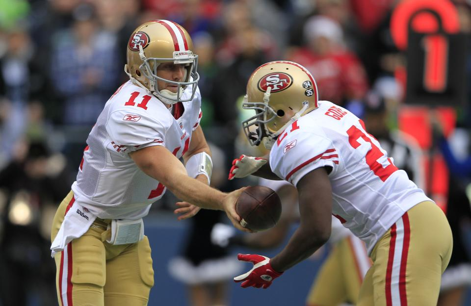 San Francisco 49ers quarterback  Alex Smith, left, hands off to  Frank Gore Seattle Seahawks in the first half of an NFL football game Saturday, Dec. 24, 2011. (AP Photo/John Froschauer)
