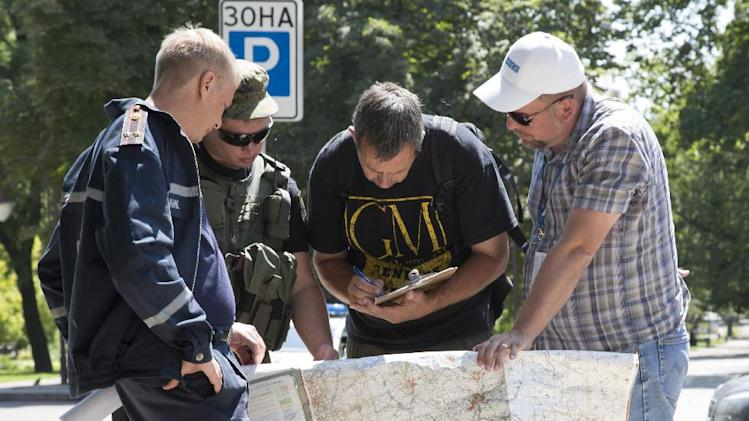 Ukrainian Ministry Emergency officer, left, Donetsk People's Republic fighter, 2nd left, and members of the OSCE mission in Ukraine examine a map as they discuss the situation around the site of the crashed Malaysia Airlines Flight 17 in the city of Donetsk, eastern Ukraine Sunday, July 27, 2014. A team of international police officers that had been due to visit the site of the Malaysian plane disaster in eastern Ukraine cancelled the trip Sunday after receiving reports of fighting in the area. Alexander Hug, the deputy head of a monitoring team from the OSCE in Europe, said it would be too dangerous for the unarmed mission to travel to the site from its current location in the rebel-held city of Donetsk. (AP Photo/Dmitry Lovetsky)