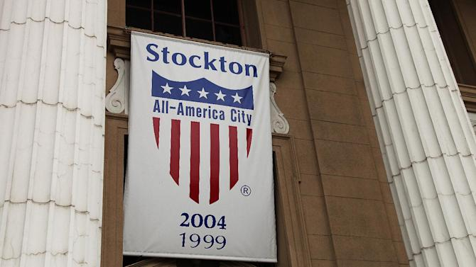 """A banner proclaiming Stockton as an All-America city hangs from city hall Wednesday, Feb. 29, 2012, in Stockton, Calif. A red, white and blue sign declaring Stockton an """"All-America City"""" still adorns City Hall, but the building's crumbling facade tells the real story of the community's recent fortunes. Since the sign went up nearly a decade ago, Stockton has twice topped Forbes magazine's list of """"America's most miserable cities."""" And now another unflattering title could be headed its way: largest American city to declare bankruptcy. (AP Photo/Ben Margot)"""