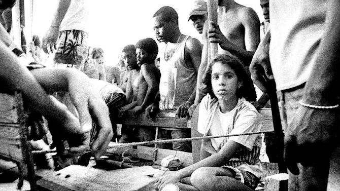 In this 1994 photo made by William Castellanos, a young girl looks solemnly out of a wooden raft. Thousands of Cubans were building makeshift rafts and throwing them into the sea after then-President Fidel Castro said anyone who wanted to leave could flee. Castellanos grabbed his old F-3 Nikon camera and began taking photos. Castellanos now lives in Miami and is working on an exhibit of his images. (AP Photo/William Castellanos)