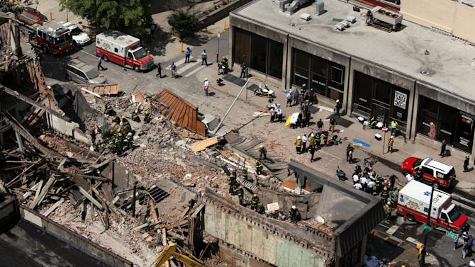Rescue personnel work the scene of a building collapse in downtown Philadelphia, Wednesday, June 5, 2013.  A four-story building being demolished collapsed Wednesday on the edge of downtown, injuring 12 people and trapping two others, the fire commissioner said. Rescue crews were trying to extricate the two people who were trapped, and the dozen people who were injured were taken to hospitals with minor injuries, according to city Fire Commissioner Lloyd Ayers. (AP Photo/Jacqueline Larma)