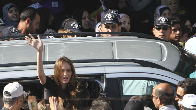 Angelina Jolie, Hollywood actress and goodwill ambassador for the U.N. High Commissioner for Refugees, UNHCR, waves as she exits a van surrounded by Syrian refugees at the Altinozu refugee camp, Turkey, near the Syrian border, Friday, June 17, 2011. U.N. envoy Angelina Jolie traveled to Turkey's border with Syria to meet some of the thousands of Syrian refugees. (AP Photo/Selcan Hacaoglu)