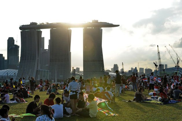 Singaporeans gathered at the Marina Barrage roof top to watch an aerial display during the 45th National Day anniversary celebrations in Singapore. (AFP photo)