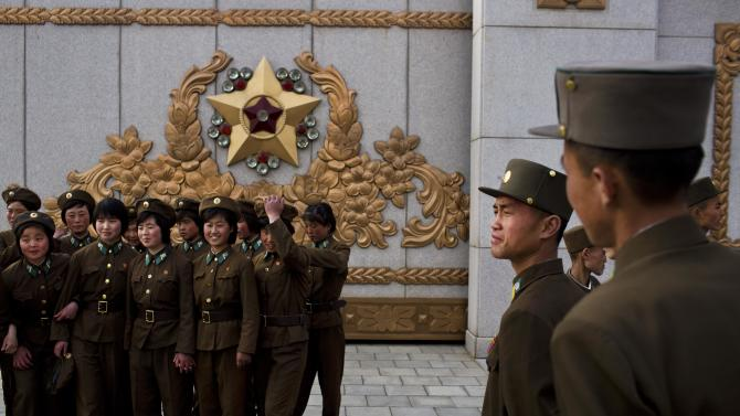 North Korean soldiers pose for souvenir photos as they tour the grounds of Kumsusan Palace of the Sun, the mausoleum where the bodies of the late leaders Kim Il Sung and Kim Jong Il lie embalmed, in Pyongyang on Thursday, April 25, 2013. North Korea on Thursday marked the 81st anniversary of the founding of its military, which began as an anti-Japanese militia and now has an estimated 1.2-million troops. (AP Photo/David Guttenfelder)