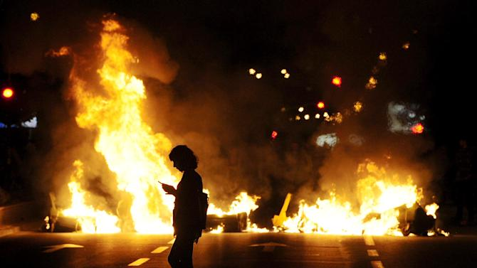 A protestor looks at his mobile phone, silhouetted against burning garbage in Skopje