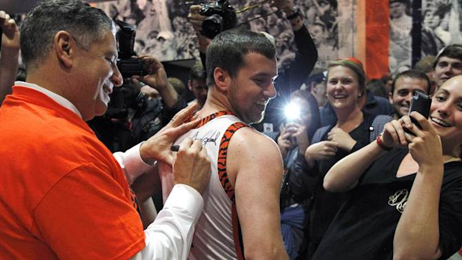 Auburn's new men's basketball coach, Bruce Pearl, autographs Clay Fleming's shirt Tuesday, March 18, 2014, in Auburn, Ala