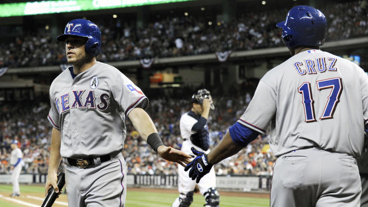 Texas Rangers' Ian Kinsler, left, is welcomed back home by Nelson Cruz (17) after scoring on a David Murphy single in the sixth inning of a baseball game against the Houston Astros Sunday, March 31, 2013, in Houston. Astros catcher Jason Castro is in the background. (AP Photo/Pat Sullivan)