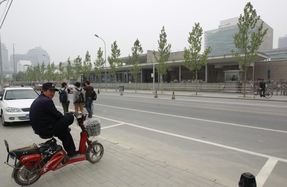 A man sits on his electric bicycle opposite to the U.S. Embassy in Beijing, China, Tuesday, May 1, 2012. A friend of blind Chinese activist Chen Guangcheng says police have acknowledged to him that Chen did not break any laws by escaping from house arrest and apparently entering the U.S. Embassy.(AP Photo/ Vincent Thian)