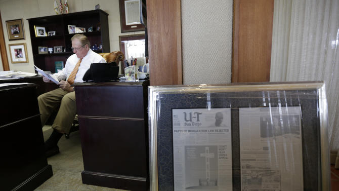 "In this photo taken Oct. 10, 2012, John Lynch, CEO of the U-T San Diego newspaper, reads mail in his office in San Diego. Lynch and his partner Douglas Manchester gave their 143-year-old newspaper a new slogan — ""The World's Greatest Country & America's Finest City"" — ran a front-page editorial that declared their plan to reshape the city's downtown waterfront their highest priority, and forecast doom if President Barack Obama wins re-election. (AP Photo/Gregory Bull)"