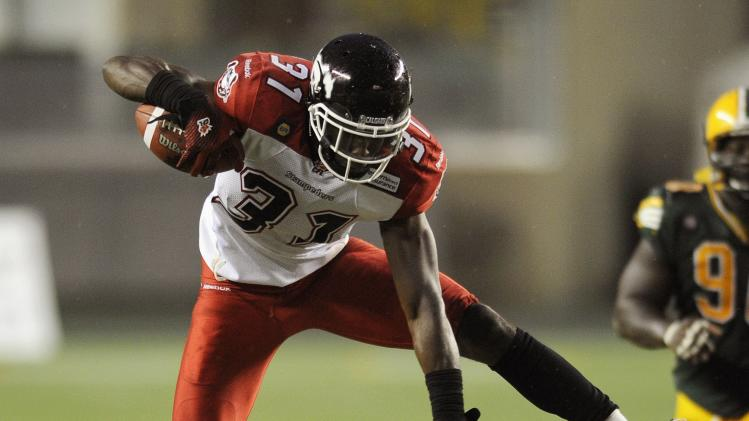 Stampeders' Fuller leaps over Eskimos' McCoil during their CFL football game in Edmonton