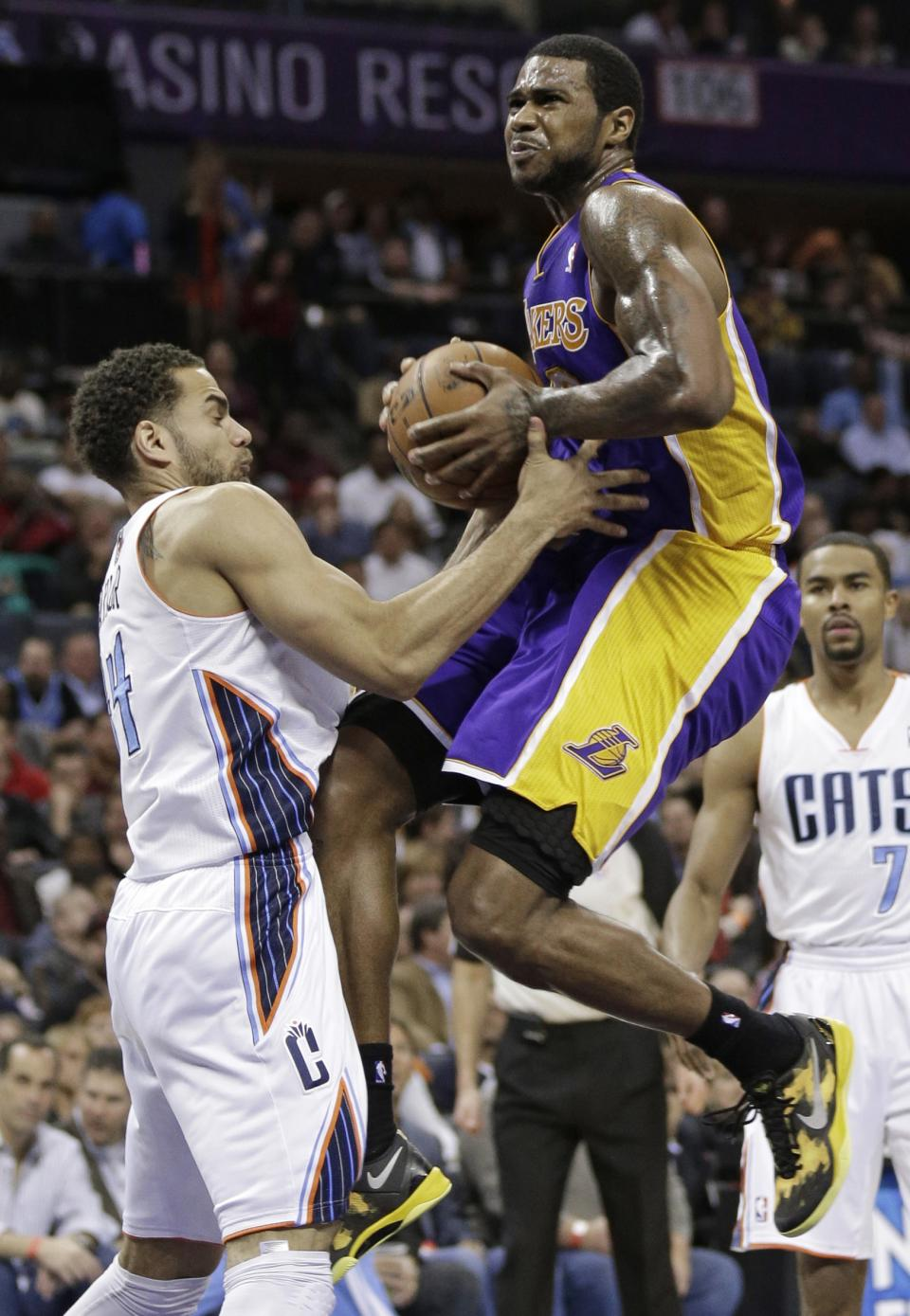 Los Angeles Lakers' Earl Clark, right, is fouled by Charlotte Bobcats' Jeffery Taylor, left, during the second half of an NBA basketball game in Charlotte, N.C., Friday, Feb. 8, 2013. The Lakers won 100-93. (AP Photo/Chuck Burton)