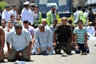 An Egyptian presidential guard officer (2nd right) prays with civilians outside Cairo's Al-Azhar mosque
