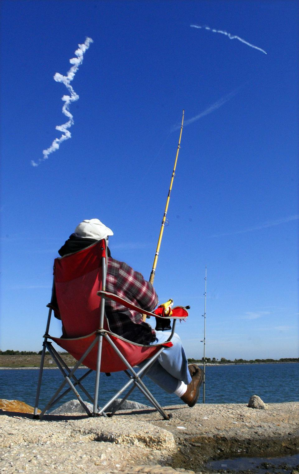 Frank Harrigan of Cocoa, Fla., does some fishing Wednesday morning Dec. 8, 2010 at Jetty Park in Cape Canaveral as the SpaceX Falcon 9 rocket is launched from Cape Canaveral Air Force Station for its first NASA demonstration flight. (AP Photo/ Florida Today, Craig Rubadoux)