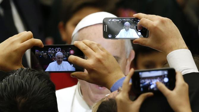 Pope Francis is pictured by mobile phones as he arrives to lead a special audience for Vatican employees and their families at the Paul VI's hall at the Vatican