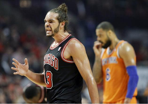 Chicago Bulls center Joakim Noah, left, reacts after Derrick Rose scored a basket as New York Knicks center Tyson Chandler is at right during the first half of an NBA basketball game in Chicago, Thurs