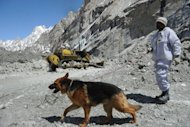 A Pakistani soldier works with a sniffer dog to search for avalanche victims during an ongoing operation at the Gayari camp near the Siachen glacier on April 18, 2012. Pakistani rescuers have recovered the first bodies from the site of an avalanche that buried 140 people at a high-altitude army camp more than seven weeks ago, the military said Sunday