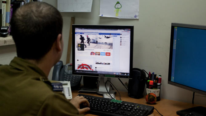 """FILE - In this Thursday, Nov. 15, 2012 file photograph, an Israeli soldier looks at the Facebook page of the Israel Defense Force, at the IDF spokesperson's office in Jerusalem. In a media bunker, attached to Israel's press office, hundreds of volunteers work around the clock on every major social media platform to produce and post instant videos and graphics about the latest twists in the Gaza offensive from Israel's point of view. Its Facebook site """"Israel Under Fire"""" has gained more than 24,000 """"likes"""" over the last week. (AP Photo/Sebastian Scheiner, File)"""