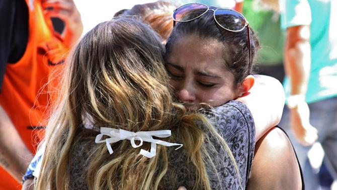 Relatives of victims react in Santa Maria city, Rio Grande do Sul state, Brazil, Sunday, Jan. 27, 2013. A blaze raced through the crowded nightclub in southern Brazil early Sunday, killing more than 200 people as the air filled with deadly smoke and panicked party-goers stampeded toward the exits, police and witnesses said. It appeared to be the world's deadliest nightclub fire in more than a decade.(AP Photo/Evandro Sturm)