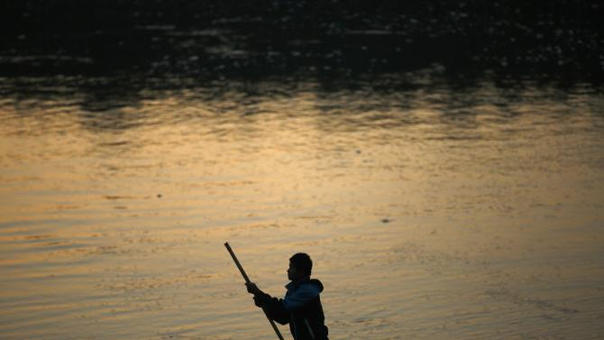 Man is silhouetted as he guides his boat with a bamboo stick to reach the bank of Rapti River at Sauraha in Chitwan