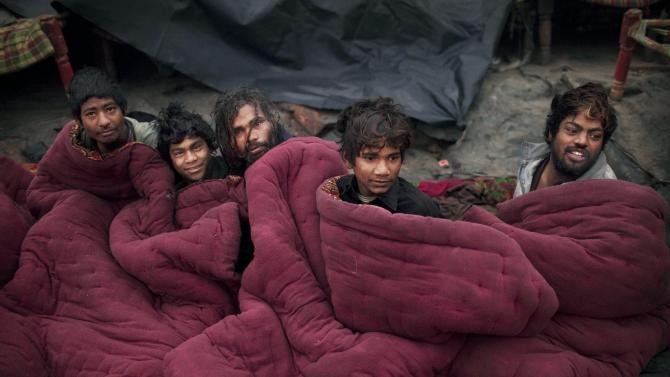 In this photo taken on Jan. 19, 2012, Indian squatters sit together in a rented blanket after waking up at Park No. 2 near Jama Masjid in New Delhi, India. For thousands of people struggling at the bottom of India's working class, the Meena Bazaar parking lot and the handful of places like it scattered across New Delhi are cheap refuges in a city where many migrants can't even afford to rent slum shanties. (AP Photo/Kevin Frayer)