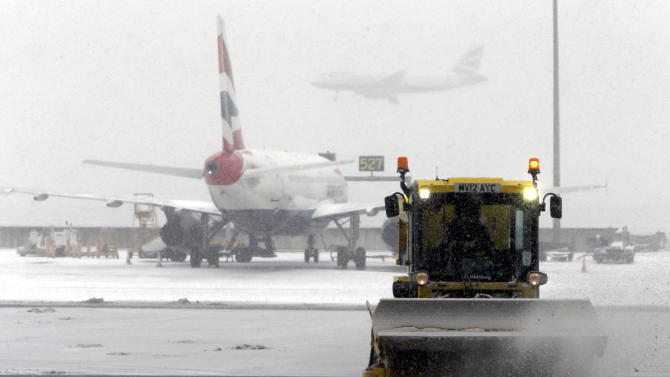 A snow plough clears snow from Heathrow Airport, London  Friday Jan. 18, 2013. Heathrow Airport briefly shut a runway and cancelled dozens of flights as a snowstorm caused widespread travel disruption across Britain.  Heathrow's northern runway re-opened Friday after being shut down briefly for de-icing and snow clearing. Some 180 flights were cancelled by midday. Rail traffic was disrupted and roads were forced to close amid plunging temperatures and icy conditions.   (AP Photo/Steve Parsons/PA) UNITED KINGDOM OUT