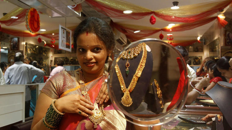 In this Thursday, Feb. 14, 2013 photo, an Indian woman looks into a mirror as she tries out gold jewelry at a shop in Mumbai, India. Nowadays, India is by far the world's biggest buyer of gold, which despite its rising value, is an increasing drain on an economy that is growing too slowly to reduce widespread poverty. Last year Indians imported 864 tons of gold, about one fifth of world sales. The cost of 2.5 trillion rupees ($45 billion) was second only to India's bill for oil imports. The unquenchable appetite for gold coins, bars and jewelry has swelled India's trade deficit and weakened its currency, making crucial imports such as fuel more expensive. (AP Photo/Rajanish Kakade)