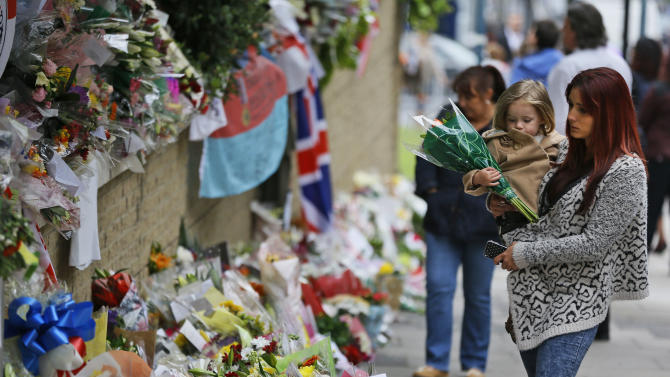 People look at some of the thousands of floral and other tributes left in honour of murdered 25-year-old British soldier Lee Rigby, at the scene near Woolwich Barracks in London, Wednesday, May 29, 2013. Two men attacked and killed the off-duty soldier in broad daylight, Wednesday, May 22. They were shot by police and arrested on suspicion of murder. (AP Photo/Lefteris Pitarakis)